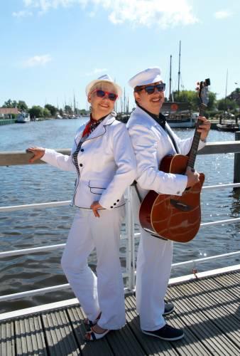 Gesangsduo maritim vor Flusshintergrund